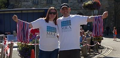 Nicola and Gleen stand in front of Battle abbey with arms frill of medals ready for the finishers of the BBB10k