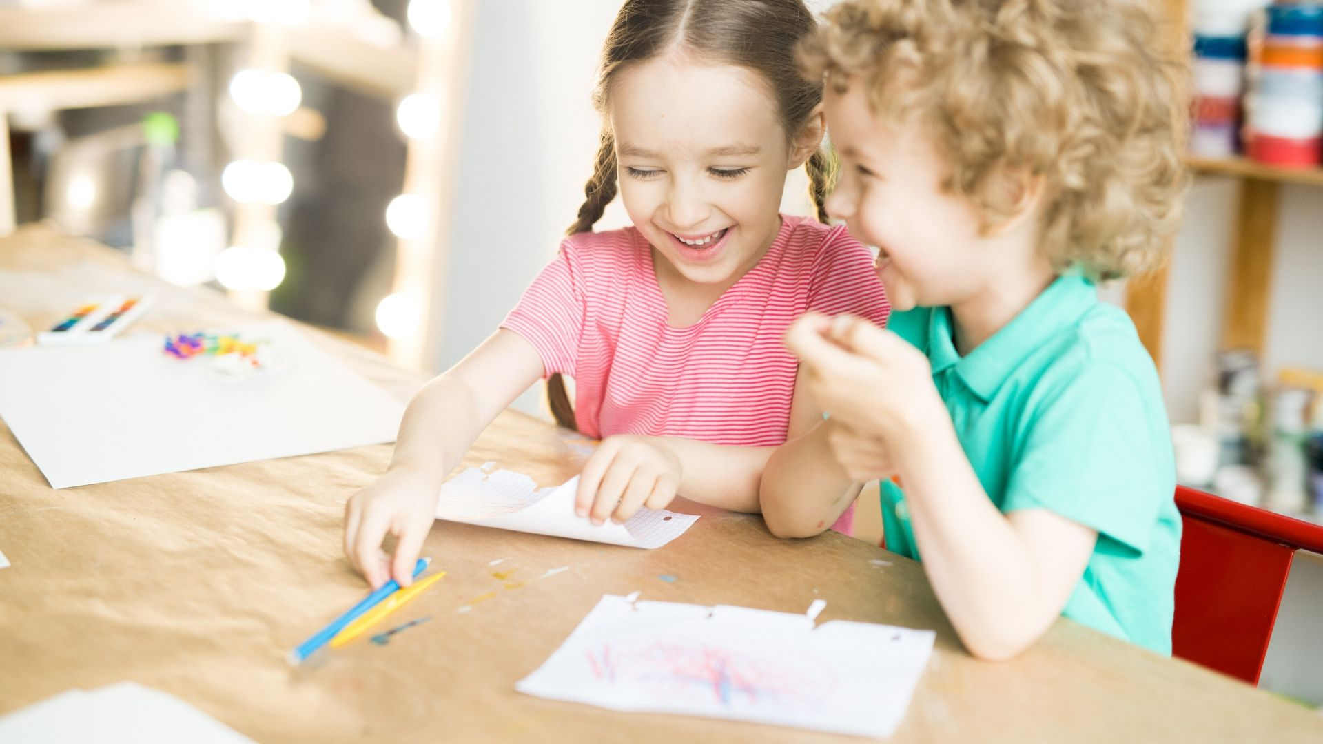 two children laughing at a table while drawing