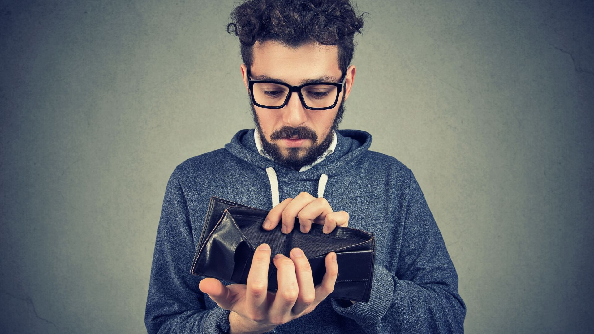 man looking at his empty wallet trying to figure out how to save money fast