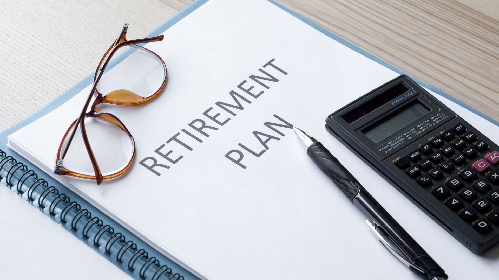 Image of a folder with the words 'retirement plan' printed on the front with a calculator, pen and glasses also on the desk