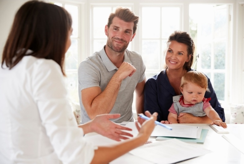 a couple with a baby speaking to a financial advisor