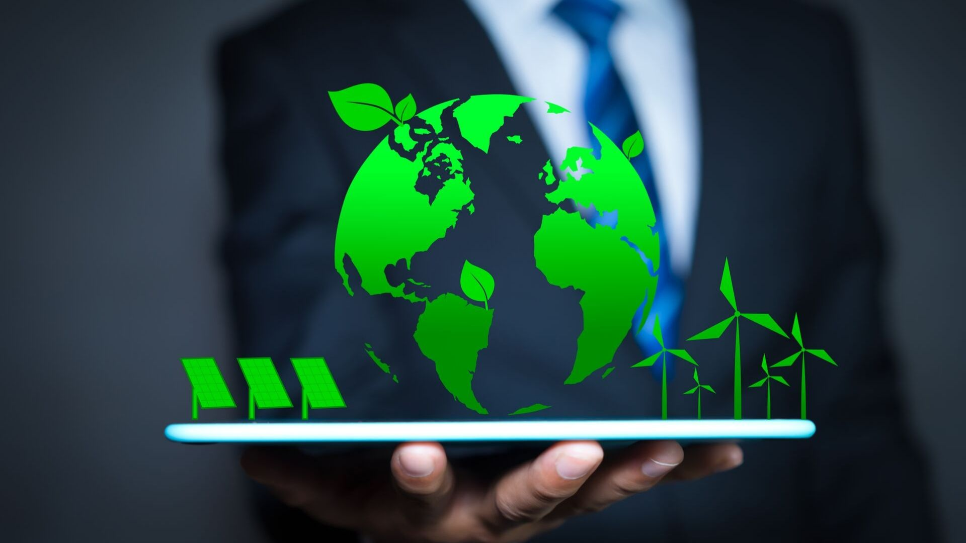 close up of a suited person holding a graphic of the world, solar panels and wind turbines in green.