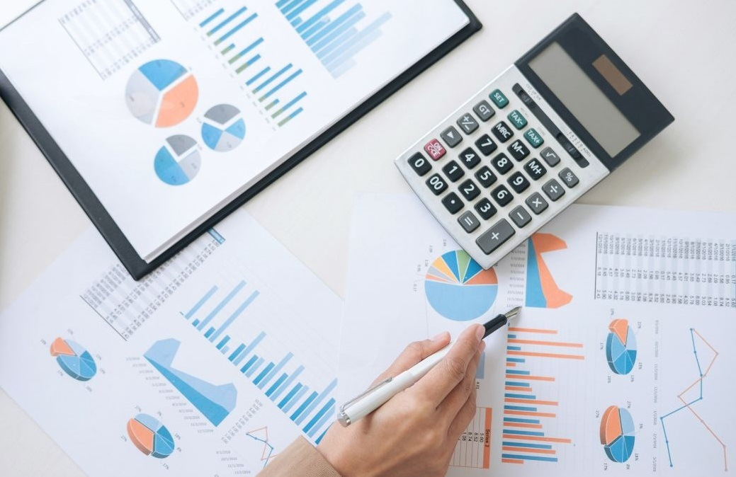 Image of a desk with print outs of financial charts and a calculator. A hand holding a fountain pen is poised over one of the charts.