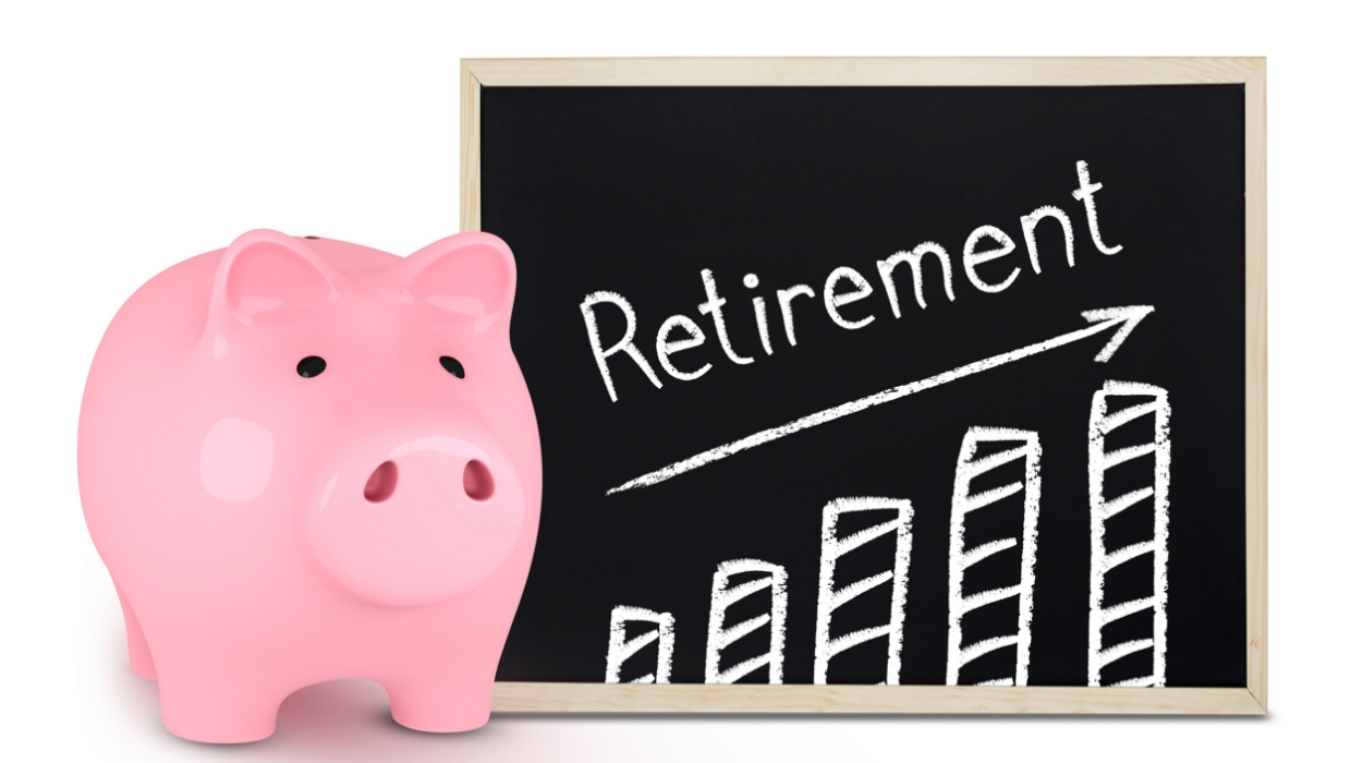 A pik ceramic piggy bank stands next to a chalk board with a bar chart going up on it and the word retirement with an arrow pointing up.