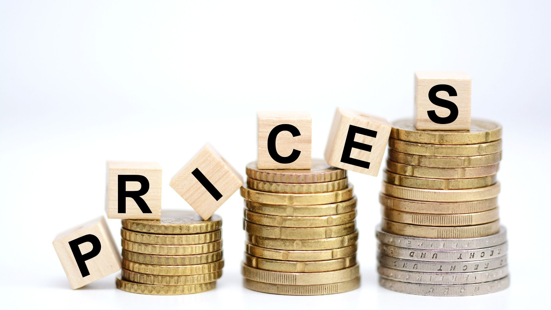 Image of 3 coin towers all increasing in height with the word 'prices' spelled out in wooden blocks on top of the coins