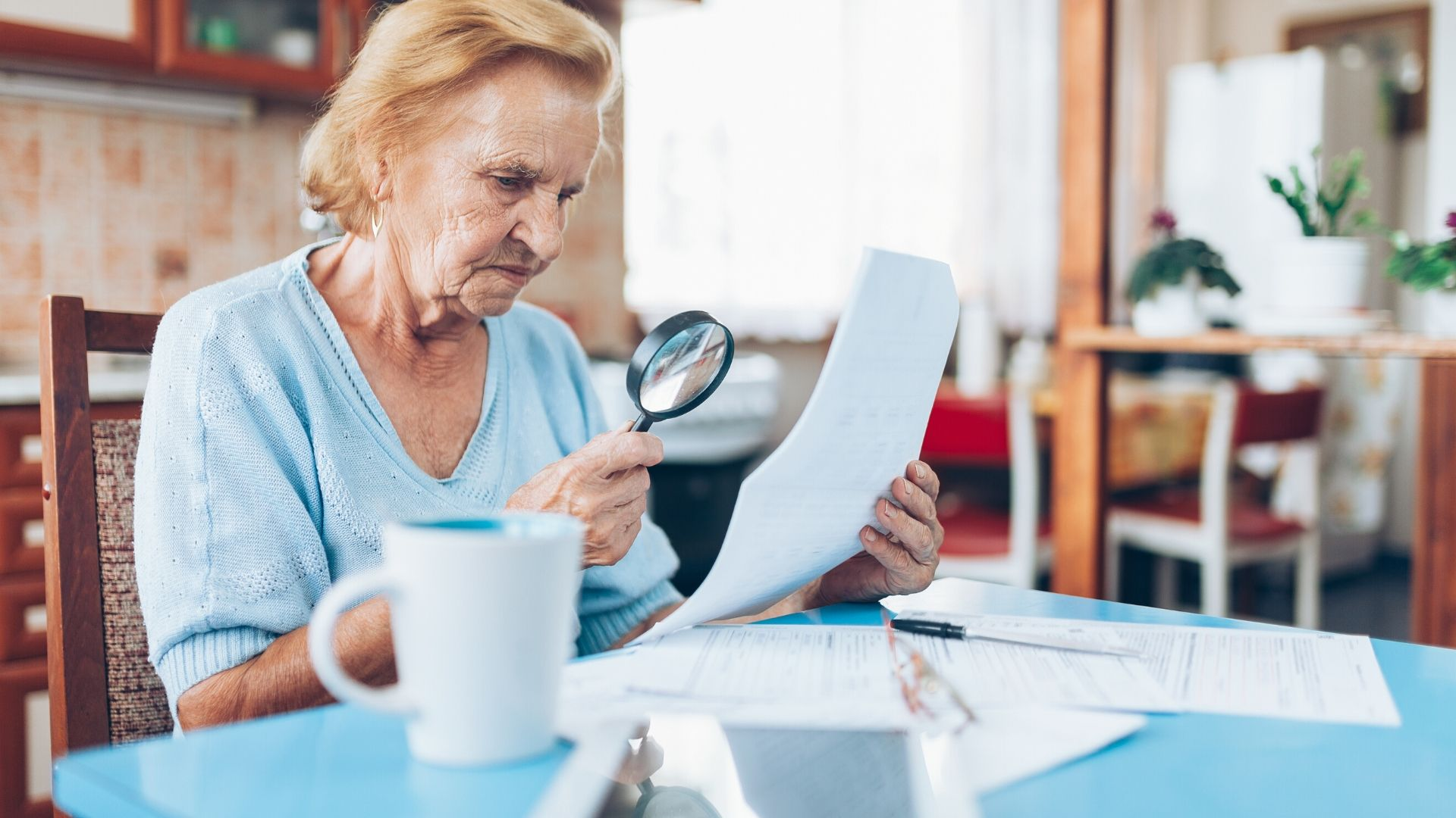 Older woman checking her bank statements for Direct Debit fraud