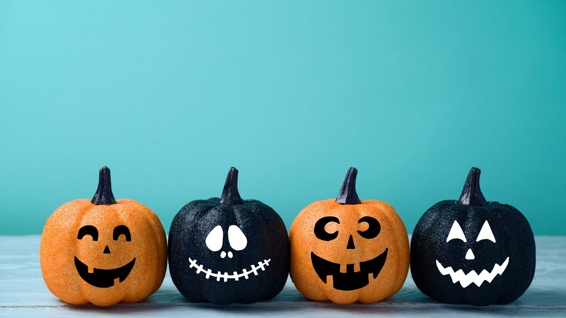 Financial Advisors are not as scary as you thinkImage of four pumpkins, two orange and two black with faces on with a teal coloured background