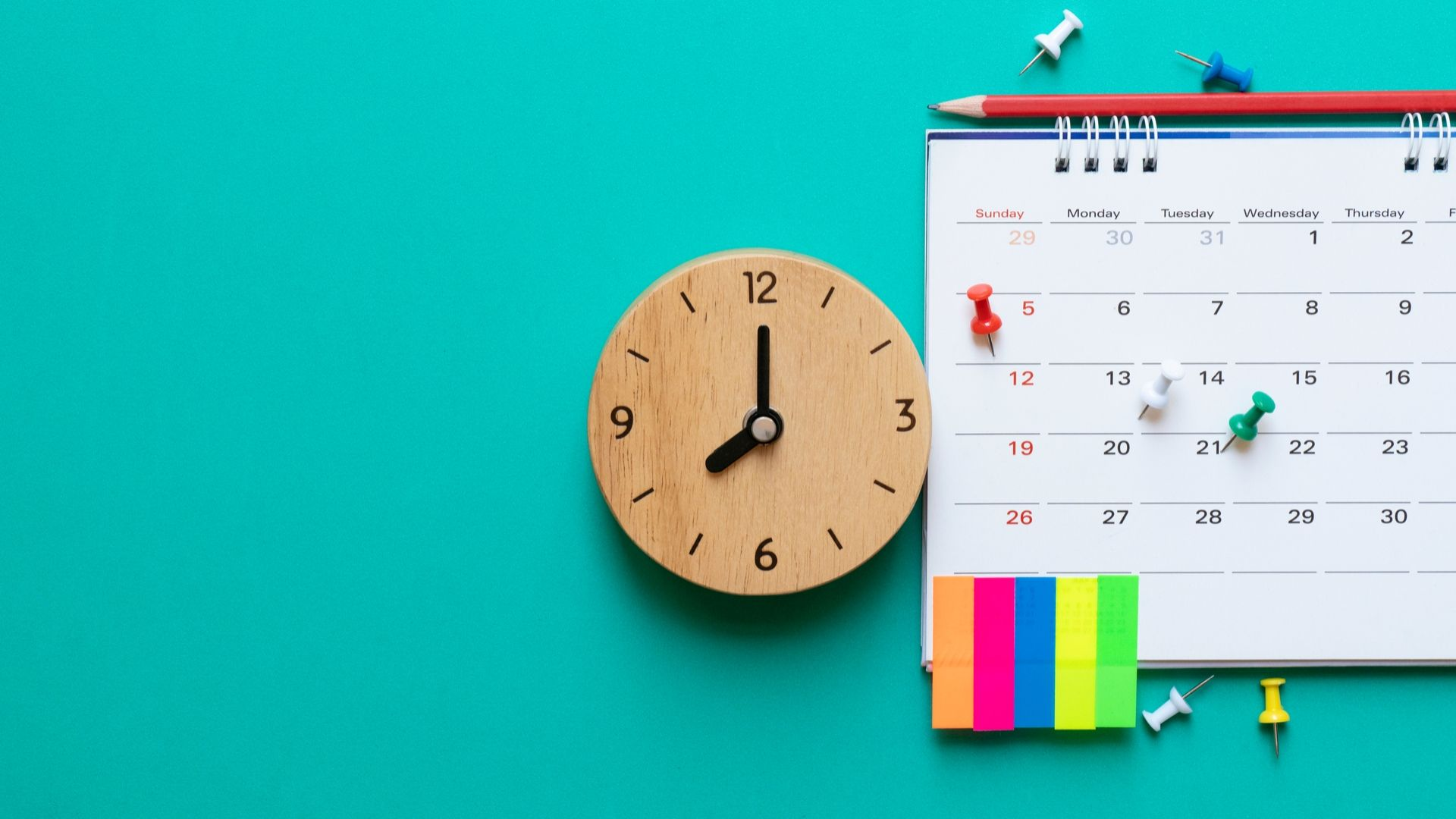 desk calendar, small wooden clock, drawing pins and coloured labels on a teal background