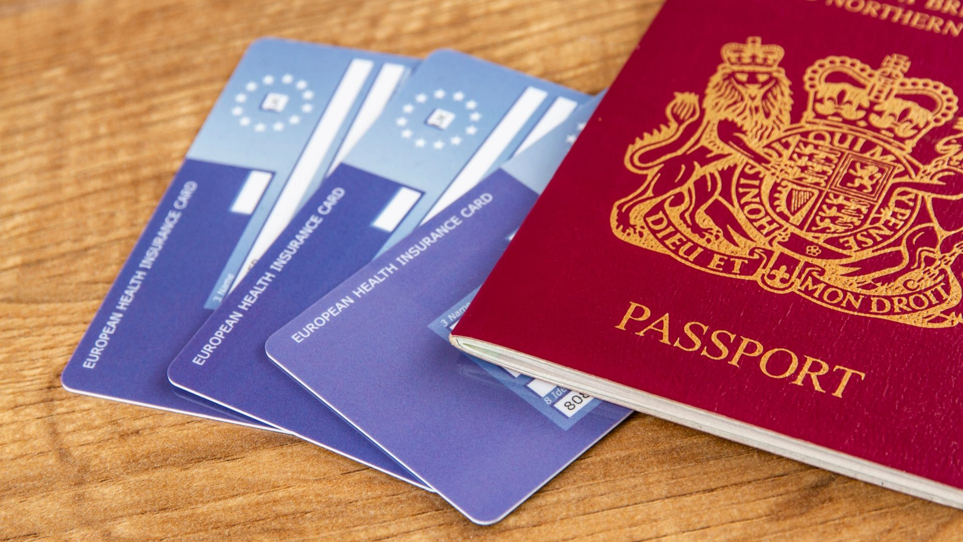 Image of three EHIC cards and a British passport fanned out on a brown wooden desk