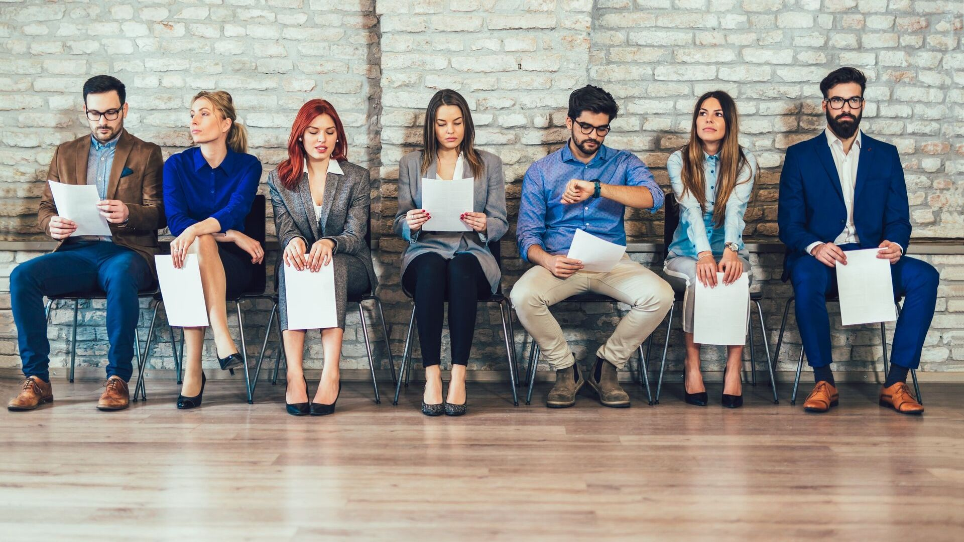 line of people sitting on chairs waiting for job interview