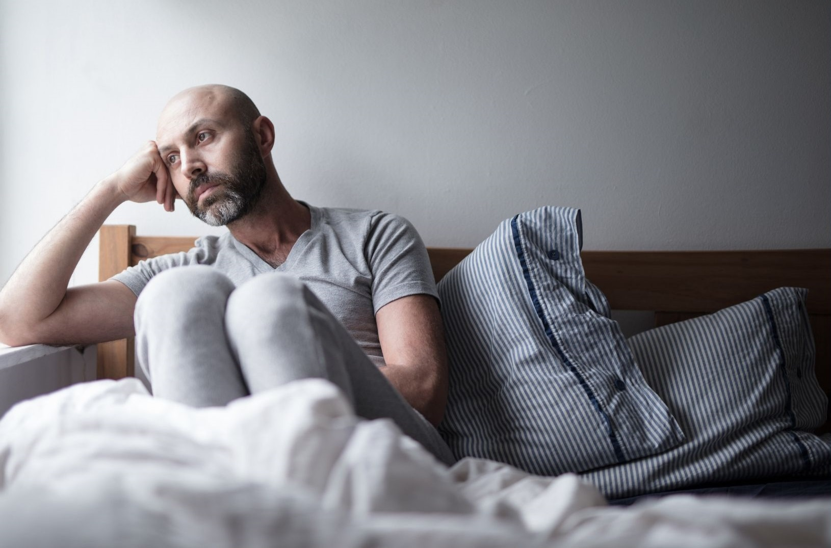 man in bed looking worried